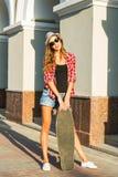 Mujer joven hermosa en gafas de sol con el patín, forma de vida de la moda de la calle Fotos de archivo
