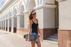 Mujer joven hermosa en gafas de sol con el patín, forma de vida de la moda de la calle Imagenes de archivo