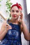 Mujer joven hermosa en guardapolvos del dril de algodón y pañuelo que mira la cámara como el espejo, Chupa Chups lamiéndose y Imagen de archivo
