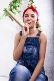 Mujer joven hermosa en guardapolvos del dril de algodón y pañuelo que mira la cámara como el espejo, Chupa Chups lamiéndose y Foto de archivo