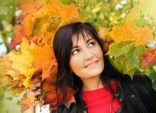Mujer joven hermosa en hojas de arce Fotografía de archivo libre de regalías