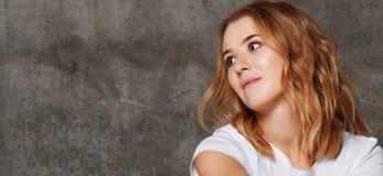 Mujer joven hermosa en la camiseta que mira lejos la cámara aislada contra fondo del muro de cemento foto de archivo