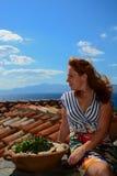 Mujer joven hermosa en la ciudad de Monemvasia que se sienta en un tejado Grecia imagenes de archivo
