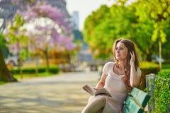 Mujer joven hermosa en la lectura de París en el banco al aire libre fotografía de archivo