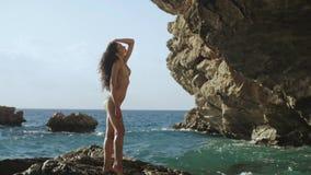 Mujer joven hermosa en la playa rocosa salvaje almacen de metraje de vídeo