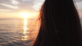 Mujer joven hermosa en la puesta del sol de observación de la playa metrajes