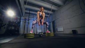 Mujer joven hermosa en la ropa de deportes gris Begins que hace ejercicio con el peso Ajuste de la cruz almacen de metraje de vídeo