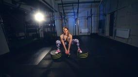 Mujer joven hermosa en la ropa de deportes gris Begins que hace ejercicio con el peso Cámara lenta metrajes