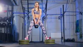 Mujer joven hermosa en la ropa de deportes gris que hace ejercicio con el peso Ajuste de la cruz almacen de video