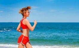 Mujer joven hermosa en la ropa de deportes que corre en la playa imagen de archivo