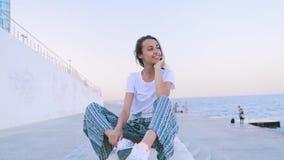 Mujer joven hermosa en la ropa ligera del verano que se sienta en el embarcadero en el puerto en el amanecer La hembra cauc?sica  almacen de metraje de vídeo