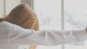 Mujer joven hermosa en la ventana en una camisa blanca baile y relajación almacen de metraje de vídeo