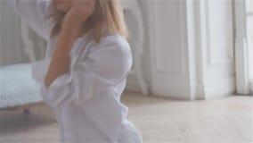 Mujer joven hermosa en la ventana en una camisa blanca almacen de metraje de vídeo
