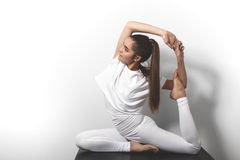 Mujer joven hermosa en la yoga que presenta en asana en un fondo del estudio Fotos de archivo