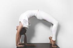 Mujer joven hermosa en la yoga que presenta en asana en un fondo del estudio Imagenes de archivo