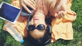 Mujer joven hermosa en las gafas de sol que mienten en la hierba, escuchando el teléfono móvil de la música y de las aplicaciones Fotos de archivo