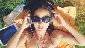Mujer joven hermosa en las gafas de sol que mienten en la hierba, escuchando la música Imagen de archivo libre de regalías