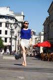 Mujer joven hermosa en los paseos dow de una blusa azul y de la falda del blanco Fotografía de archivo libre de regalías