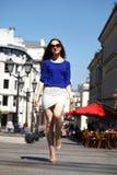Mujer joven hermosa en los paseos dow de una blusa azul y de la falda del blanco Imagen de archivo