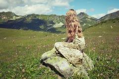 Mujer joven hermosa en montañas en un prado Foto de archivo