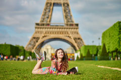 Mujer joven hermosa en París que está situada en la hierba cerca de la torre Eiffel Fotos de archivo libres de regalías