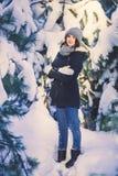 Mujer joven hermosa en parque en día de invierno que nieva Fotos de archivo libres de regalías