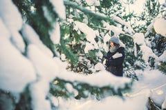 Mujer joven hermosa en parque en día de invierno que nieva Fotografía de archivo