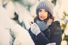 Mujer joven hermosa en parque en día de invierno que nieva Foto de archivo