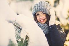 Mujer joven hermosa en parque en día de invierno que nieva Foto de archivo libre de regalías