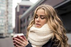 Mujer joven hermosa en parque en otoño que sonríe sosteniendo la taza de café para llevar Adolescente rubio feliz al aire libre e Imagen de archivo libre de regalías
