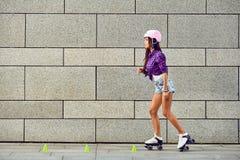 Mujer joven hermosa en pcteres de ruedas y un casco rosado Fotografía de archivo libre de regalías