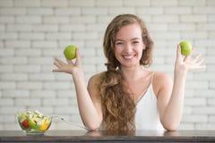 Mujer joven hermosa en posturas alegres con el cuenco de ensalada foto de archivo libre de regalías