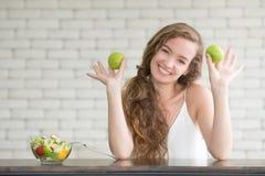 Mujer joven hermosa en posturas alegres con el cuenco de ensalada fotografía de archivo