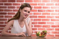 Mujer joven hermosa en posturas alegres con el cuenco de ensalada imagenes de archivo