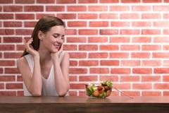 Mujer joven hermosa en posturas alegres con el cuenco de ensalada fotografía de archivo libre de regalías
