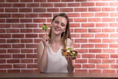 Mujer joven hermosa en posturas alegres con la mano que sostiene el cuenco de ensalada imagenes de archivo