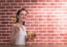 Mujer joven hermosa en posturas alegres con la mano que sostiene el cuenco de ensalada fotografía de archivo libre de regalías