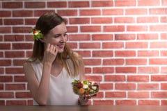 Mujer joven hermosa en posturas alegres con la mano que sostiene el cuenco de ensalada imagen de archivo