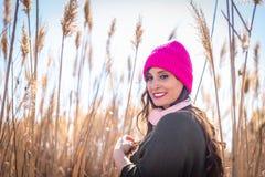 Mujer joven hermosa en un campo de la m?sica que escucha de la alta hierba imágenes de archivo libres de regalías