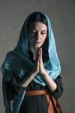 Mujer joven hermosa en un mantón azul que ruega Imagenes de archivo