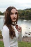 Mujer joven hermosa en un parque con el lago en fondo Foto de archivo