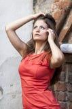 Mujer joven hermosa en un paseo rojo del cortocircuito del vestido de cóctel de la casa vieja Fotografía de archivo