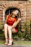 Mujer joven hermosa en un paseo rojo del cortocircuito del vestido de cóctel de la casa vieja Foto de archivo libre de regalías