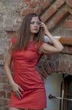Mujer joven hermosa en un paseo rojo del cortocircuito del vestido de cóctel de la casa vieja Imágenes de archivo libres de regalías