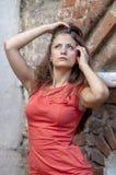 Mujer joven hermosa en un paseo rojo del cortocircuito del vestido de cóctel de la casa vieja Fotos de archivo libres de regalías