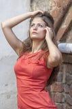 Mujer joven hermosa en un paseo rojo del cortocircuito del vestido de cóctel de la casa vieja Fotos de archivo