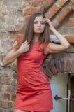 Mujer joven hermosa en un paseo rojo del cortocircuito del vestido de cóctel de la casa vieja Foto de archivo
