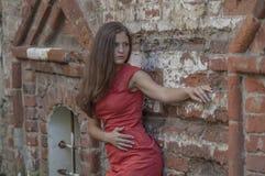 Mujer joven hermosa en un paseo rojo del cortocircuito del vestido de cóctel de la casa vieja Imagen de archivo