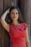 Mujer joven hermosa en un paseo rojo del cortocircuito del vestido de cóctel de la casa vieja Imagenes de archivo