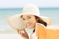 Mujer joven hermosa en un sombrero y un traje de baño sobre backgro de la playa fotografía de archivo